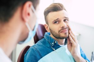 man with toothache looking to dentist for emergency care