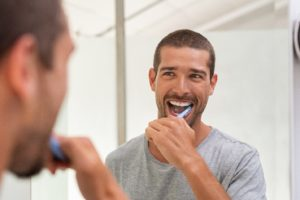 happy man following dentist's advice to brush his teeth