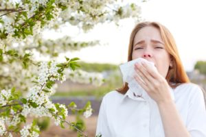 Woman standing next to tree, suffering from seasonal allergies